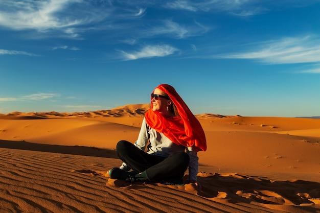 日没時のサハラ砂漠の孤独な少女。 erg chebbi、merzouga、モロッコ。 Premium写真