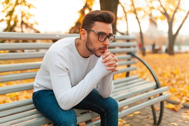 A lonely handsome man sits sad in the park on a bench. Premium Photo