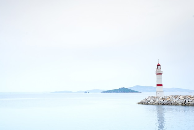 Lonely lighthouse on a stone road in the middle of the sea with views of the mountains and fog Premium Photo