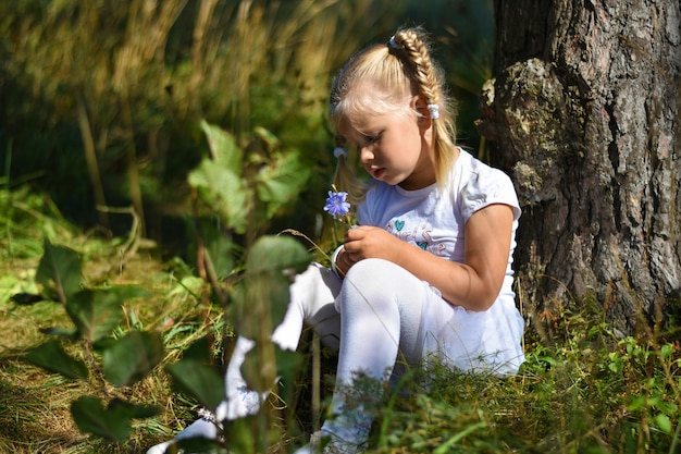 Lonely little girl in a white dress and a flower in her hand sits near a tree in the afternoon Premium Photo