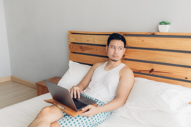 Lonely man is working with his laptop on his cozy bed. concept of freelancer work lifestyle. Premium Photo