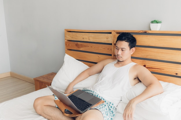 Lonely man is working with his laptop on his cozy bed. Premium Photo