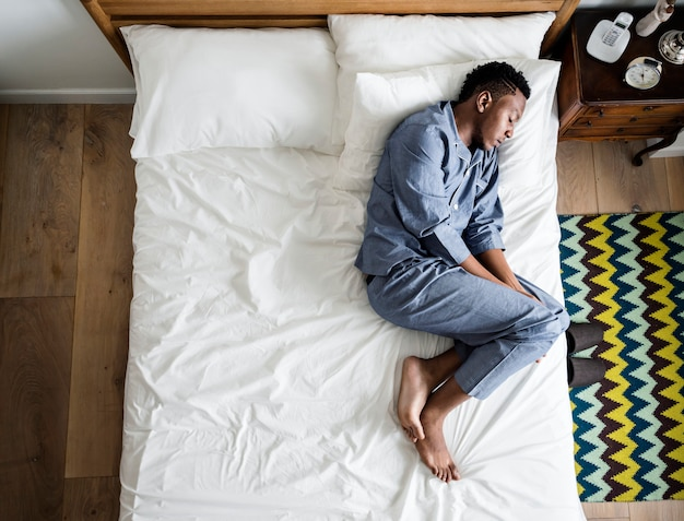 Lonely man sleeping alone on the bed Premium Photo