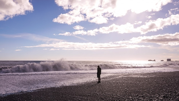 A lonely man standing at the beach Free Photo