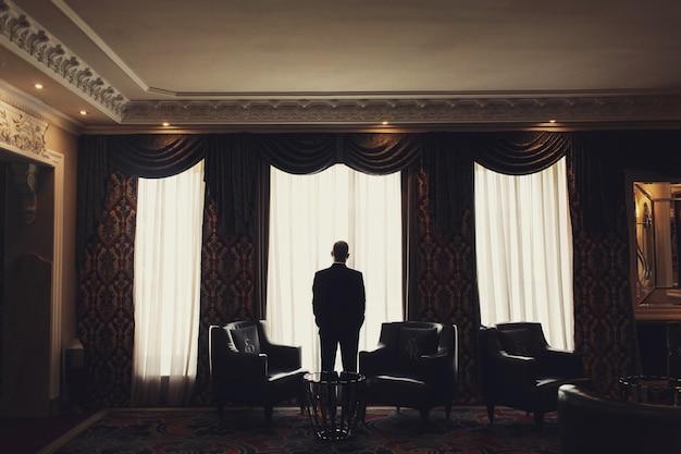 외로운 남자는 방에있는 창 앞에 서 무료 사진
