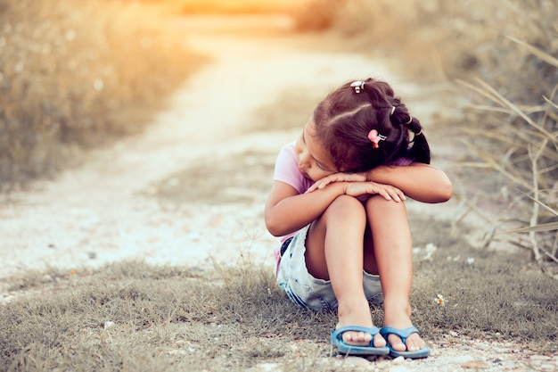 Lonely and sad little girl sitting in the park in vintage color tone Premium Photo
