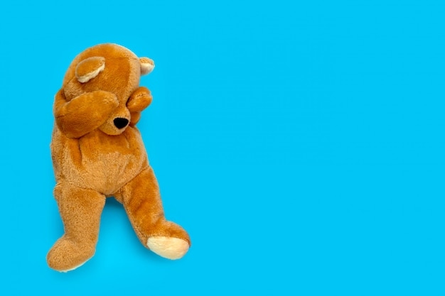 Lonely sad teddy bear on blue background. Premium Photo