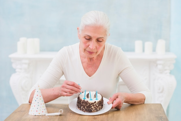 Lonely senior woman arranging candles on birthday cake at home Free Photo