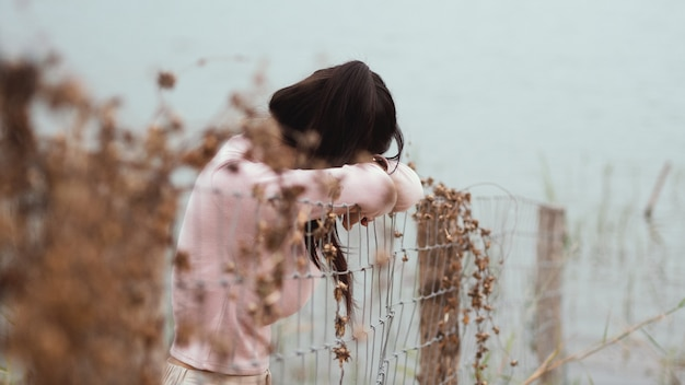 Lonely woman standing at the fence alone beside the river. lonely, sadness concept. Premium Photo