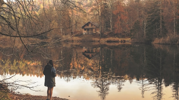 Lonely woman standing near the lake with the reflection of the isolated wooden cabin visible Free Photo