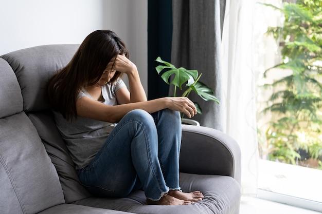 孤独な若いアジア女性が落ち込んでいると、自宅のリビングルームで否定的な感情の概念を強調 Premium写真
