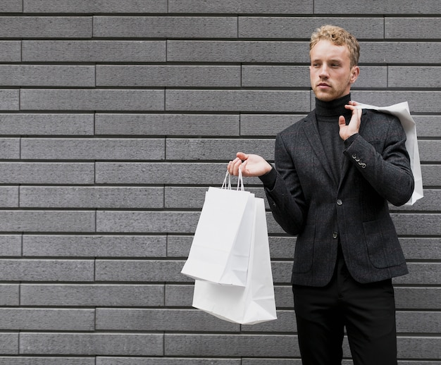 Lonely young man with shopping bags Free Photo