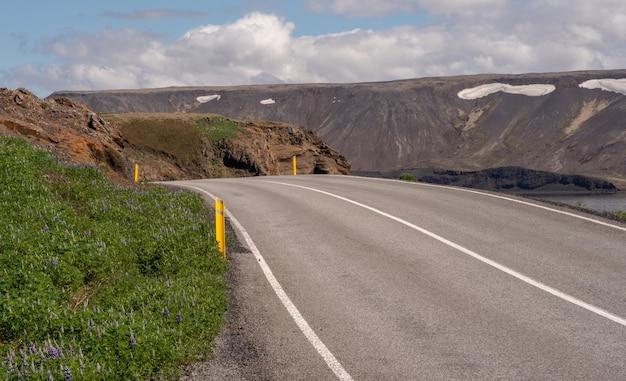 Длинная асфальтированная дорога в окружении высоких гор под облачным небом Бесплатные Фотографии