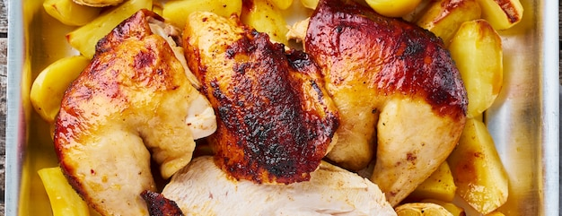 Long banner with grilled chicken meat, leg, thigh with baked potatoes, garlic. top view, close up Premium Photo