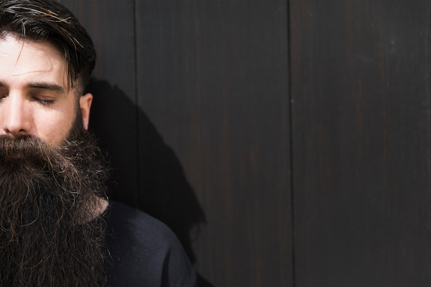 Long bearded young man with eye closed against black wall Free Photo