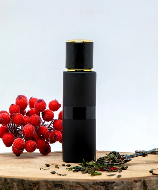 Long black perfume bottle decorated with cranberry and bergamot leaves Free Photo