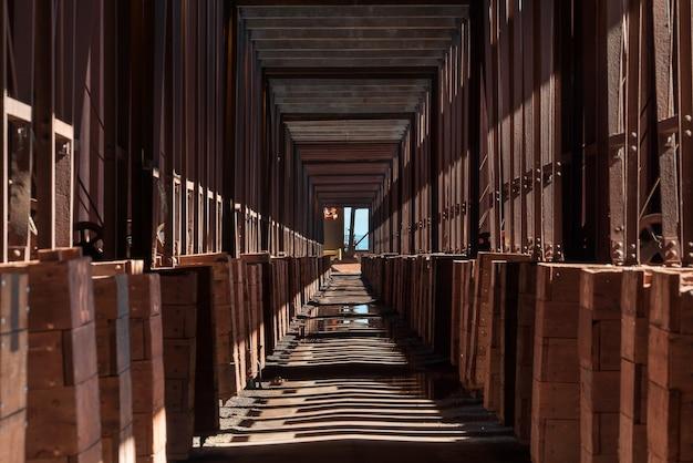 땅에 기둥의 그림자가있는 산업 건물의 긴 복도 무료 사진