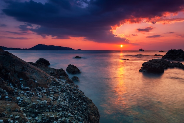Long exposure image of dramatic sky seascape with rock in sunset scenery Premium Photo