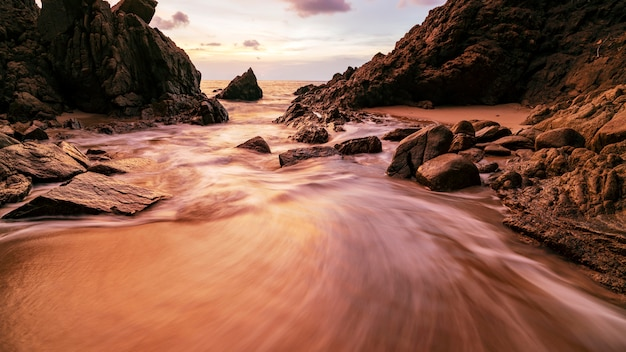 Long exposure image of dramatic sky and wave seascape with rock in sunset scenery background Premium Photo