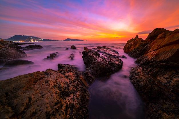 前景の日没または海の風景の背景の日の出に岩がある劇的な空の海の風景の長時間露光画像。 Premium写真