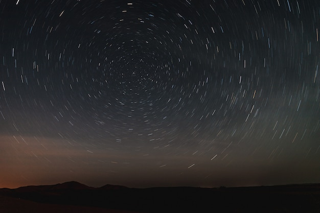 Long exposure photo of the sky in the sahara desert, looking star trails at night. Premium Photo