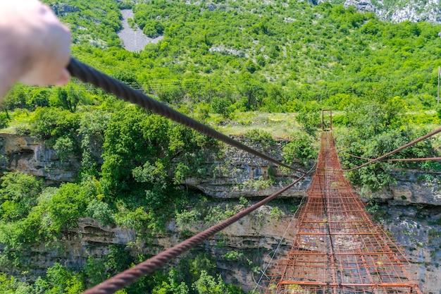 Long extreme suspension iron bridge across the river moraca. montenegro. Premium Photo