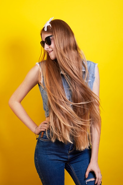 Long ginger girl in sunglasses poses on yellow background Premium Photo