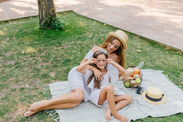 長い髪のかわいい女の子が若い母親と一緒に公園にやって来ました。ピースサインでポーズをとって、毛布の上に横たわっている娘を見てヴィンテージ帽子の笑顔の女性。 無料写真