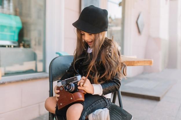Длинноволосая возбужденная маленькая девочка сидит на стуле в летнем кафе и играет с ретро камерой. открытый портрет заинтересованного фигурного ребенка, ожидающего матери-фотографа, держащего ее вещи. Бесплатные Фотографии