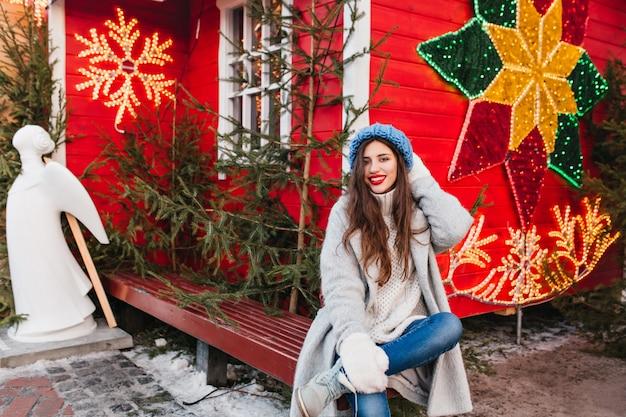 Длинноволосая женская модель сидит на деревянной скамейке возле красного дома, украшенного на рождество. привлекательная брюнетка девушка позирует после новогоднего праздника рядом с зелеными деревьями и скульптурами ангела. Бесплатные Фотографии