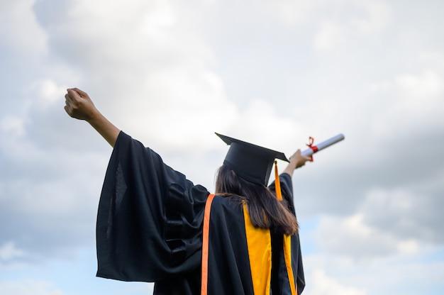 Long haired female students wearing black ruffle dresses expressing joy on graduation at the university. Premium Photo