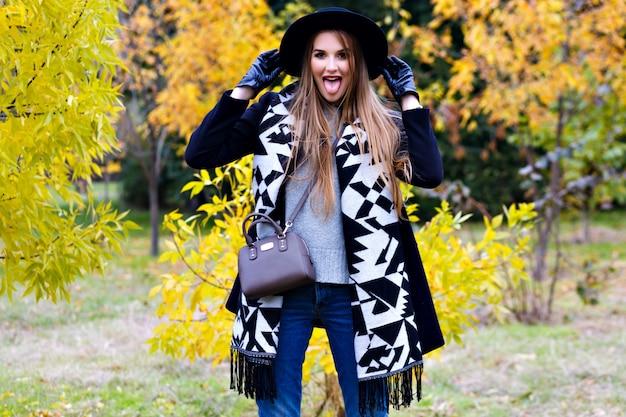 長い髪の少女は、秋の公園で彼女のスカーフで遊んでジーンズを着ています。森で過ごす時間と笑ってスタイリッシュな黒い帽子の魅力的な若い女性。 無料写真