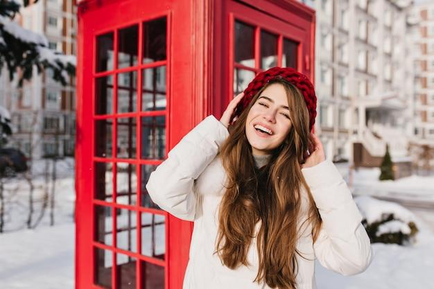 寒い日に電話ボックスの横に笑顔でポーズをとってニットベレー帽の長い髪の女性。冬の朝のコールボックスの近くに赤い帽子立っている魅力的なブルネットの女性の屋外の写真。 無料写真