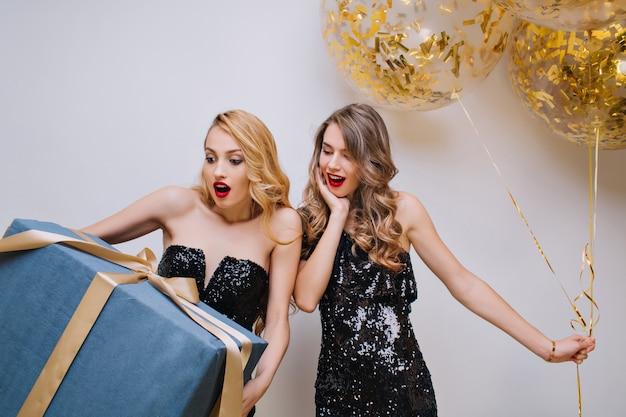 パーティー風船の束でポーズをとって、驚いた笑顔で友達を見ている長髪の素敵な女性。ショックを受けた誕生日の女の子は大きなプレゼントボックスを保持している黒いドレスを着ています。 無料写真