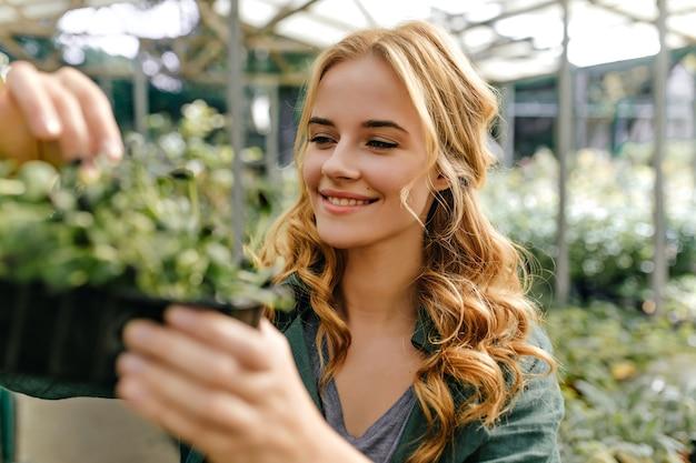 長い髪の赤毛の女の子は、彼女の手に緑の鍋を持って、幸せで心から笑顔です。植物に囲まれた外のクローズアップの肖像画。 無料写真