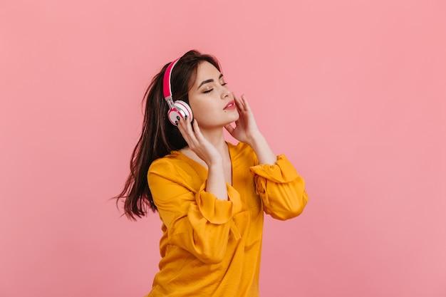 Donna dai capelli lunghi in camicetta luminosa e cuffie bianche e rosa che ascolta la musica sulla parete isolata. Foto Gratuite