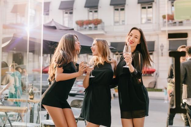 Длинноволосая женщина в модном черном боди позирует с целующим выражением лица, глядя на сестру-блондинку Бесплатные Фотографии