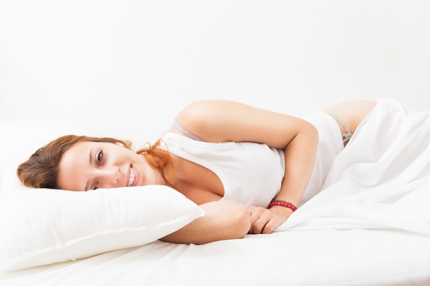 Long-haired woman lying on white sheet in bed at home Free Photo