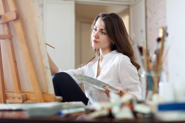 Long-haired woman paints picture on canvas Free Photo