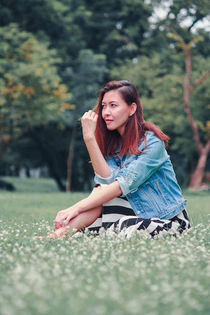 A long haired woman sitting in the lawn Premium Photo