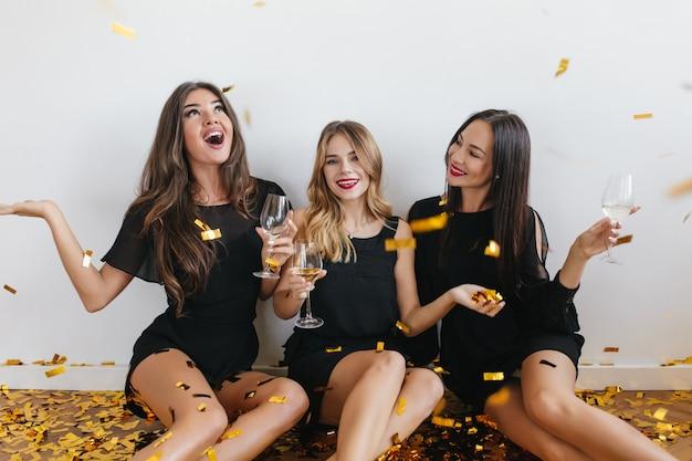 Длинноволосые женщины смотрят на конфетти с удивленным выражением лица во время вечеринки Бесплатные Фотографии