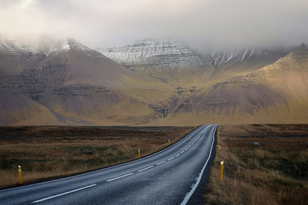 Long narrow road with beautiful hills and mountains covered in fog Free Photo