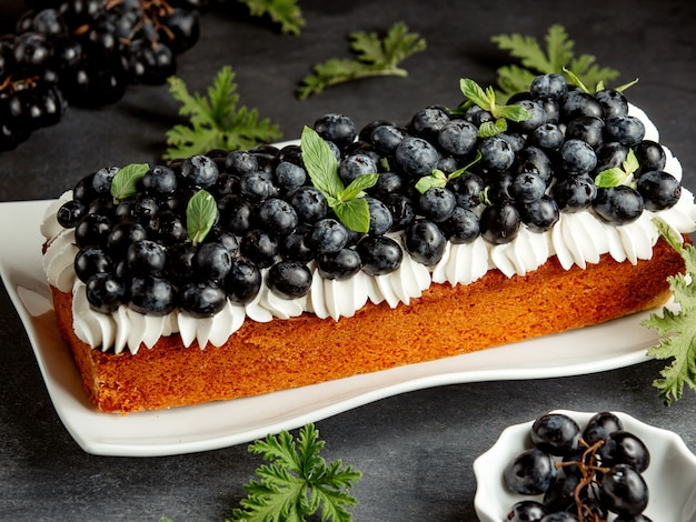 Long pie decorated with white cream and blueberries Free Photo