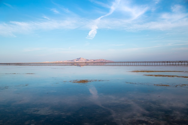 Long pier among the sea and mountains. the sky is reflected in the water. Free Photo