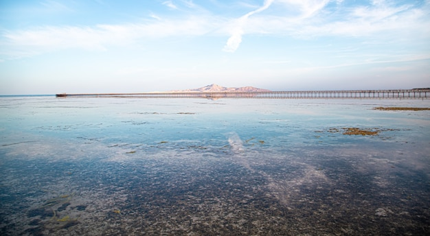 Long pier among the sea and mountains. the sky is reflected in the water. Premium Photo