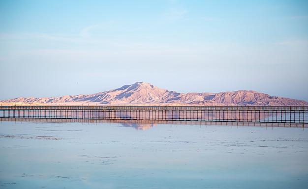 바다와 산 사이의 긴 부두. 하늘이 물에 비친다. 무료 사진