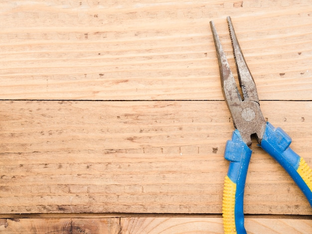 Long pliers on wooden table Free Photo