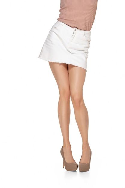 Gambe lunghe e graziose della donna isolate sulla parete bianca con copyspace. pronto per il tuo design. figura sportiva e in forma, concetto di moda e bellezza. Foto Gratuite