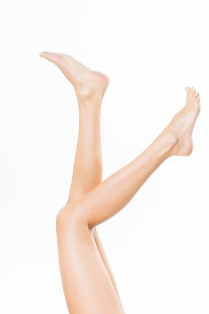 Gambe graziose lunghe della donna isolate sulla parete bianca Foto Gratuite