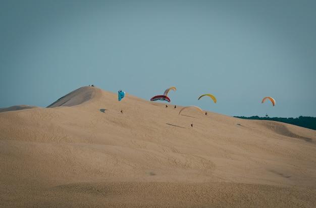맑고 푸른 하늘과 모래 언덕에 방문 패러 글라이더의 장거리 촬영 무료 사진